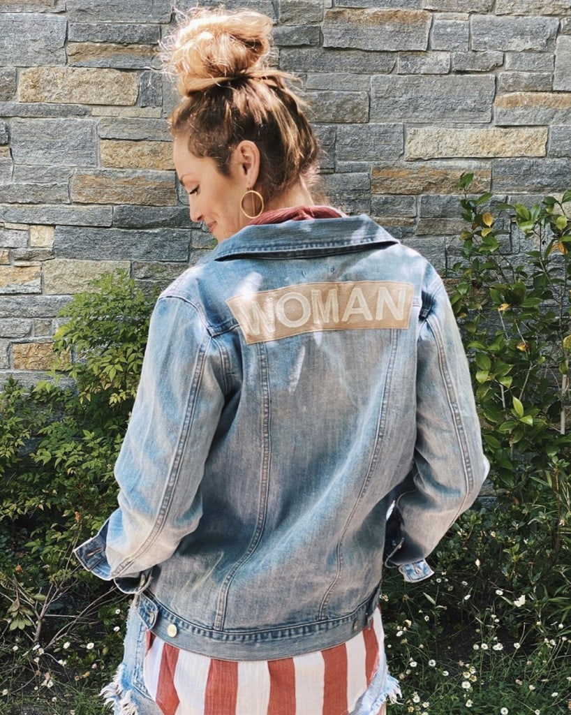 "woman stands with back to camera modeling light blue denim jacket that has the word ""woman"" in all caps embroidered"