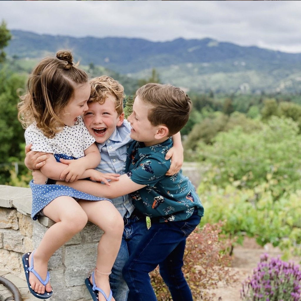 Three children embrace each other while they laugh lovingly against a backdrop of picturesque rolling green hills