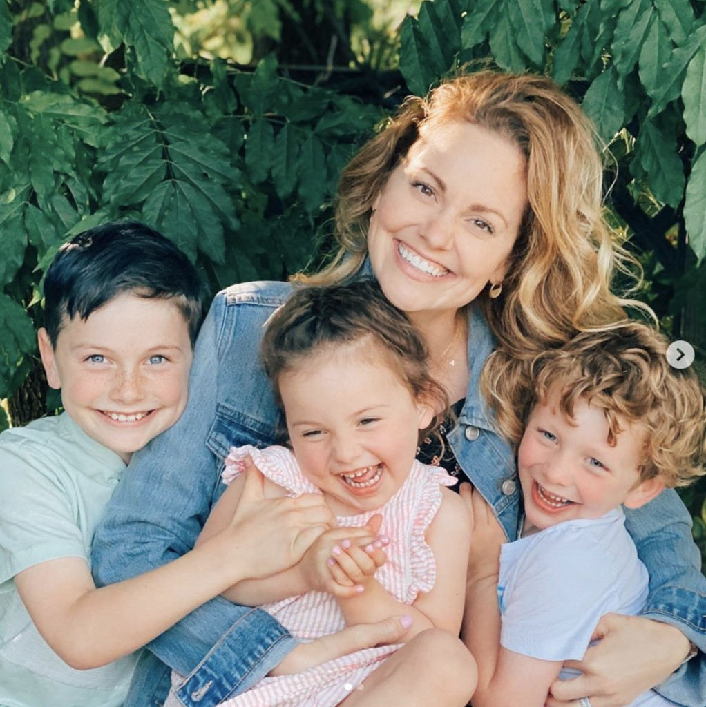Woman smiles joyfully at camera while embracing three gleeful children