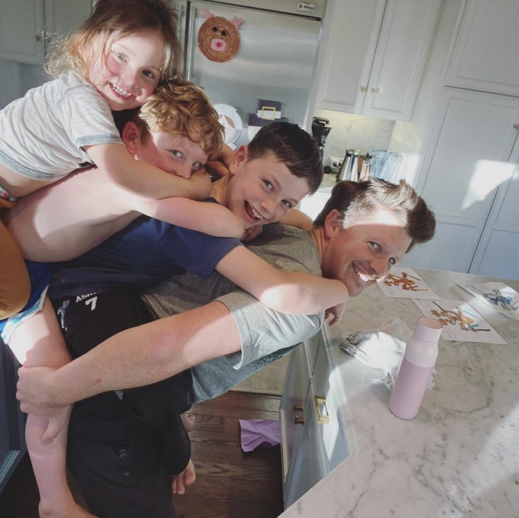 Father stands in home kitchen smiling at camera with three children playfully stacked on his back
