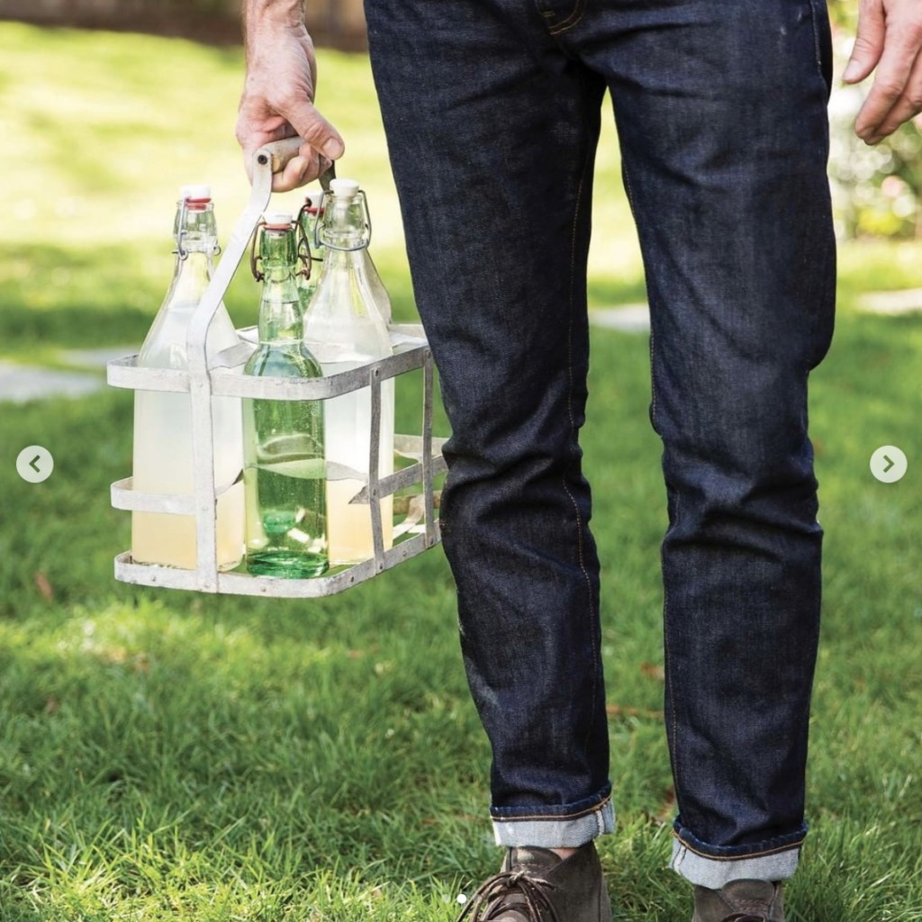 the bottom portion of a man is photographed carrying a glass bottle holder while he stands on a lawn