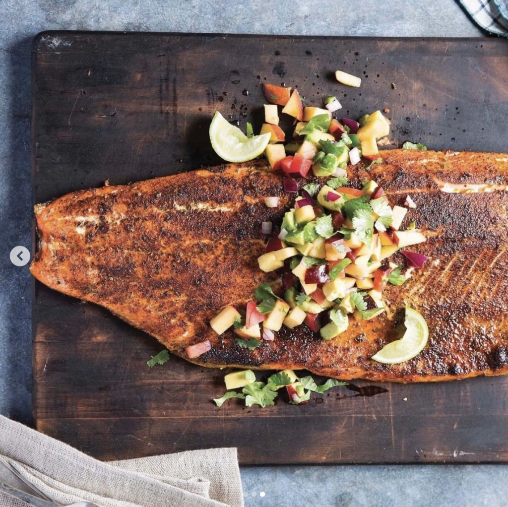 cooked blackened salmon topped with a mango avocado salsa lays on a dark wood cutting board