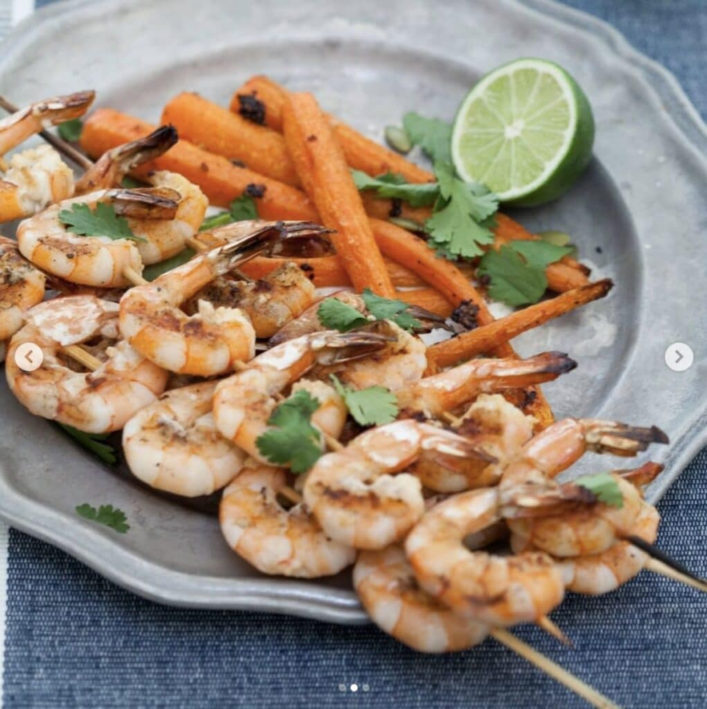 Shrimp on wooden skewers with a side of carrots, garnished with cilantro and lime on a gray dish