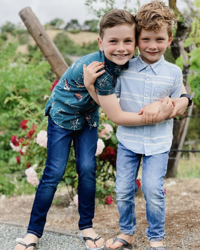 Two young male siblings embrace each other while smiling directly at the camera