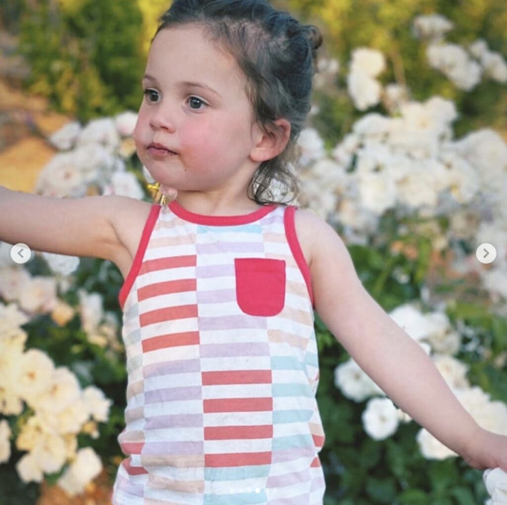 Picture of young girl wearing a striped tank top looking off camera