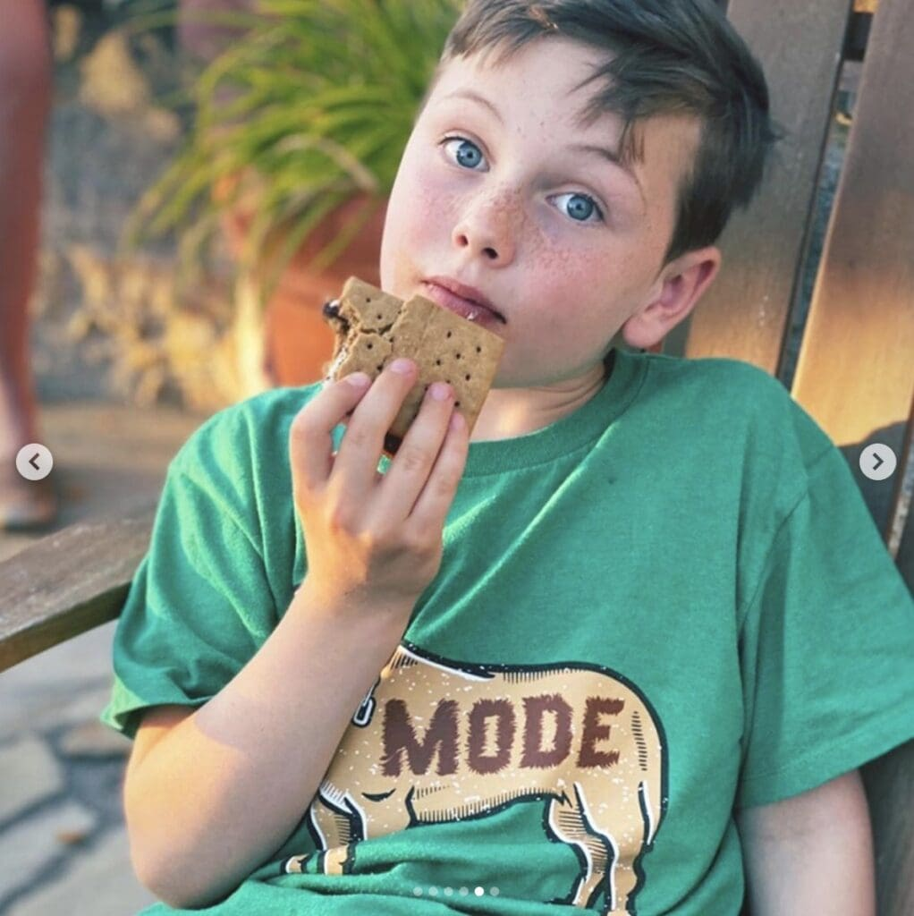 Boy wearing a green t-shirt stares seriously into camera as he gets ready to bite into his s'more