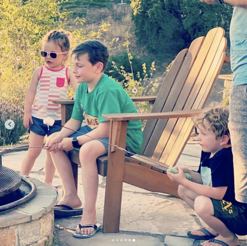 children gather around a stone fire pit to toast marshmallows