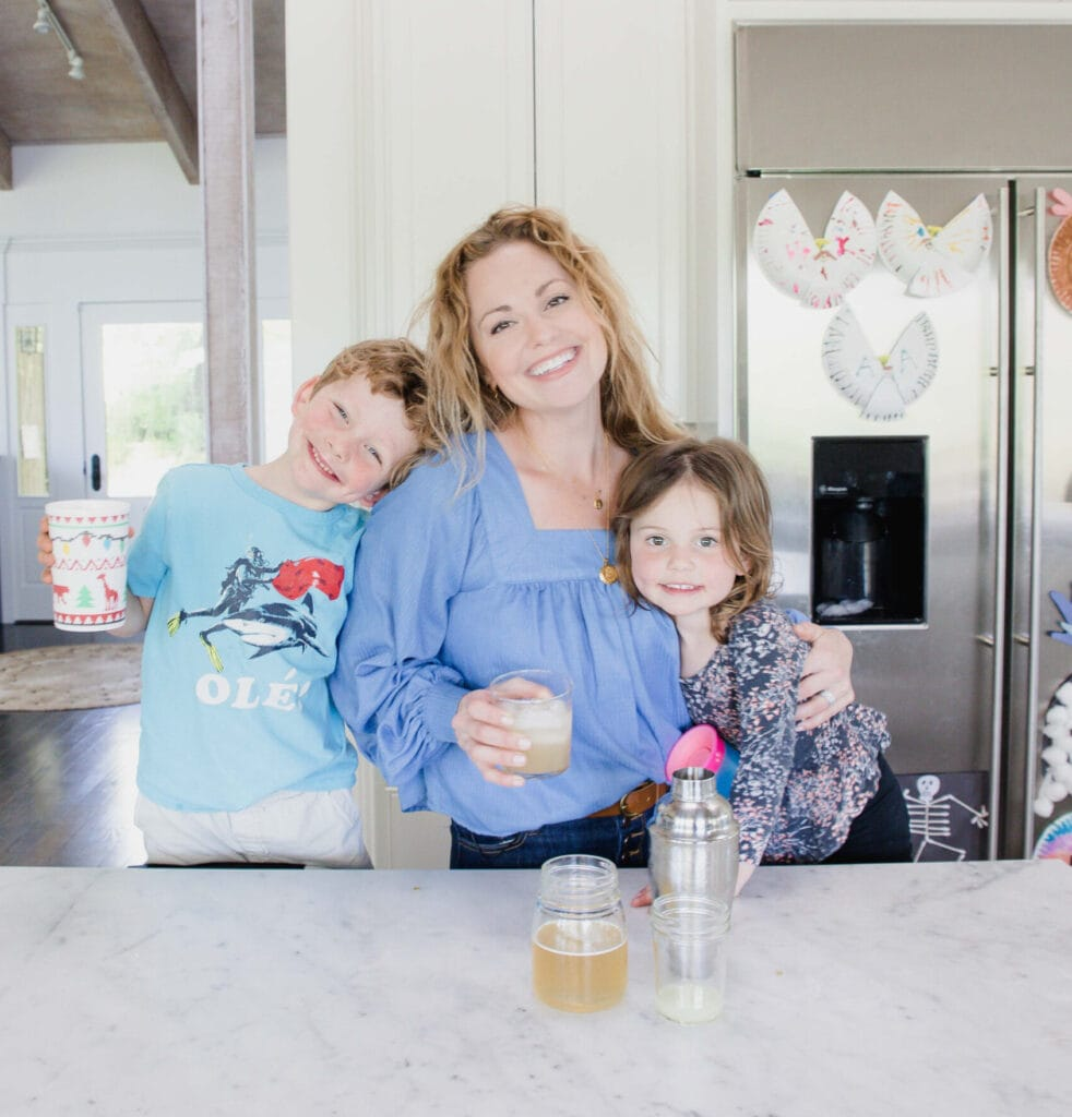 Woman stands in home kitchen smiling at camera while holding a drink in one hand & embracing her young daughter with the other. Her young son holds a kid friendly drink in his hand and leans against her as he smiles at the camera as well.