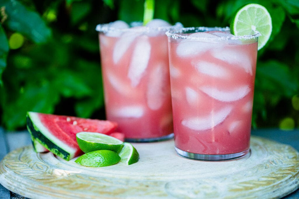 Watermelon Margaritas (Paleo & Refined Sugar-Free) served in glass tumblers full of ice and garnished with a lime next pieces of fresh watermelon