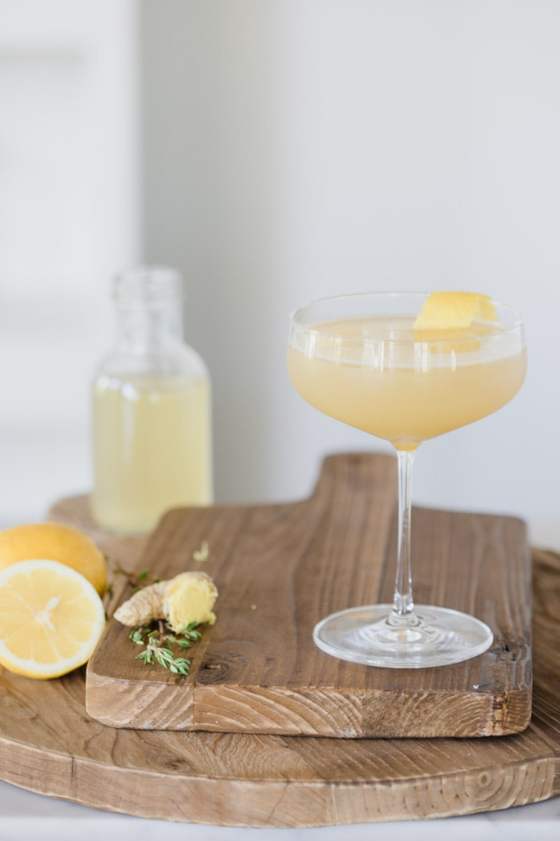 Ginger Thyme Tequila Sour cocktail garnished with lemon placed on wooden cutting boards