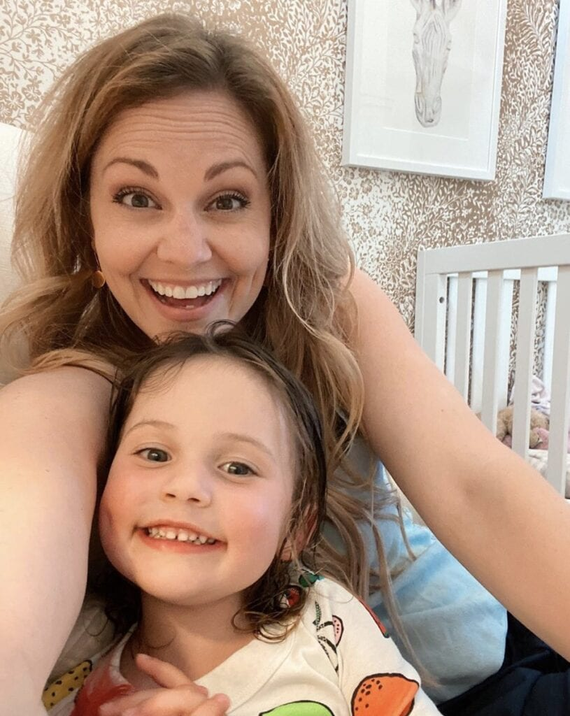 Mother and daughter smile directly at camera