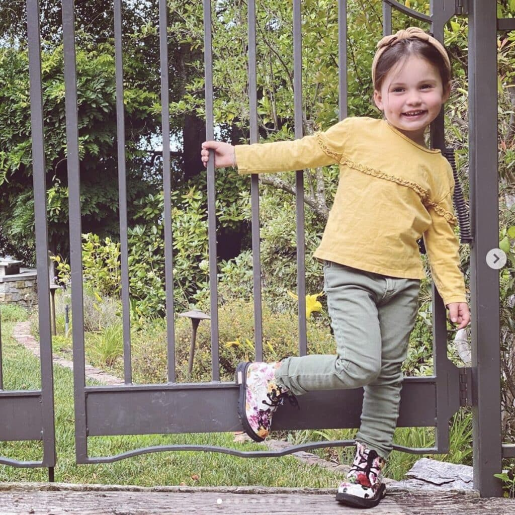 Young girl poses next to fence wearing floral combat boots, olive green jeans and a mustard yellow shirt with matching headband. She smiles directly at camera.