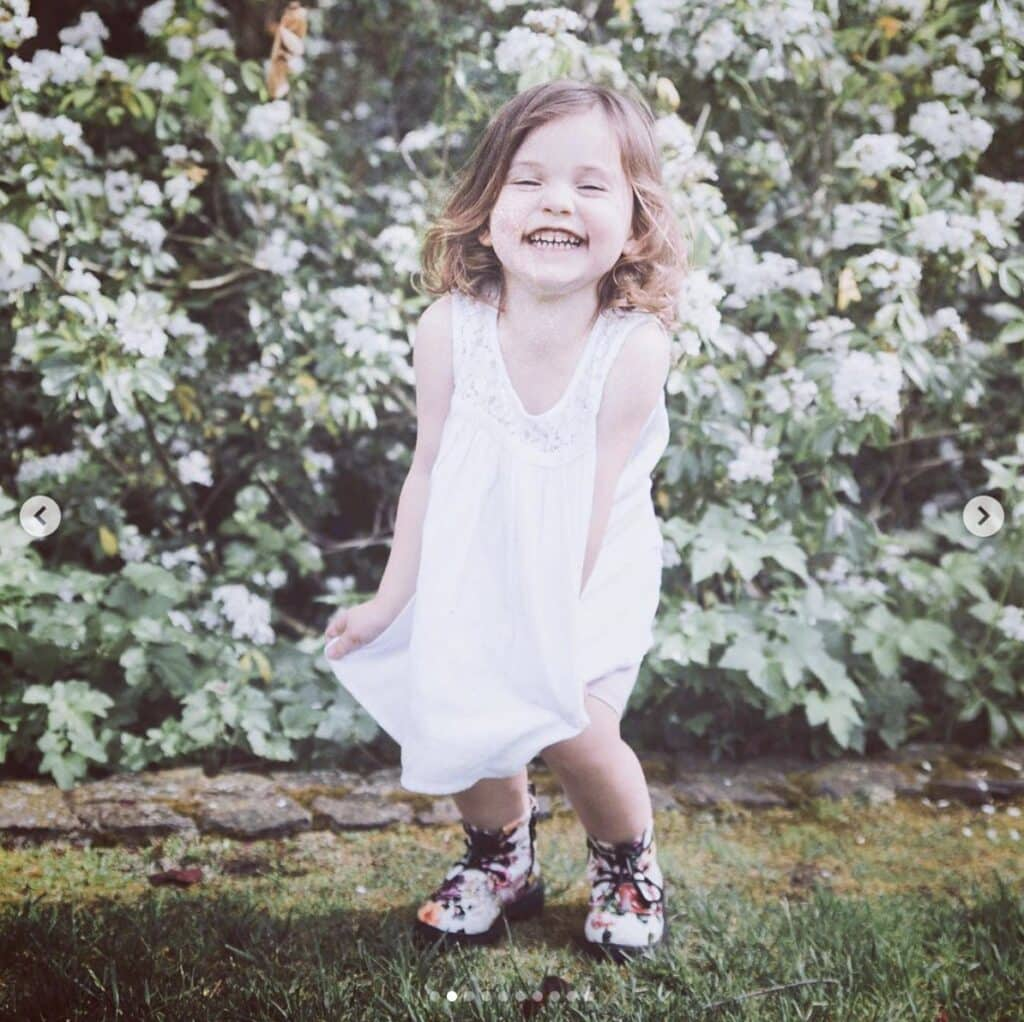 young girl laughs in front of floral bush outdoors. She's wearing floral combat boots and a white dress