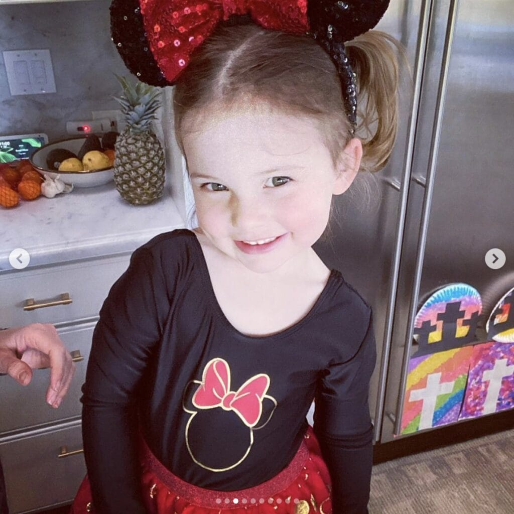 Young girl smiles at camera while standing in home kitchen. She wears a black and red Minnie Mouse tutu dress, complete with sequined ear headband