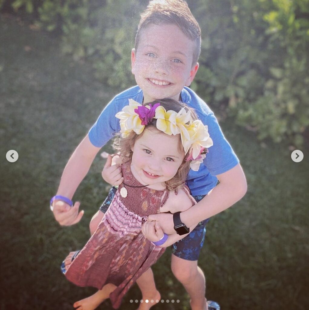 young girl wearing a flower crown is embraced by older brother. They both smile directly at the camera.