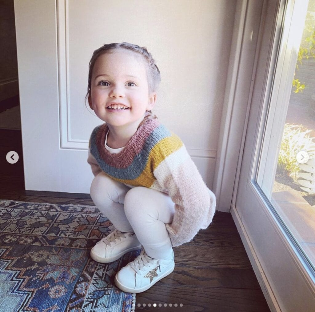 Young girl squats inside home while smiling directly at the camera. She is wearing white pants & shoes with a striped sweater.