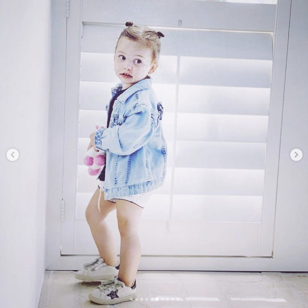 Young girl standing in home looks off camera while holding a pink and white stuffed animal. She wears shorts and sports an oversized jean jacket