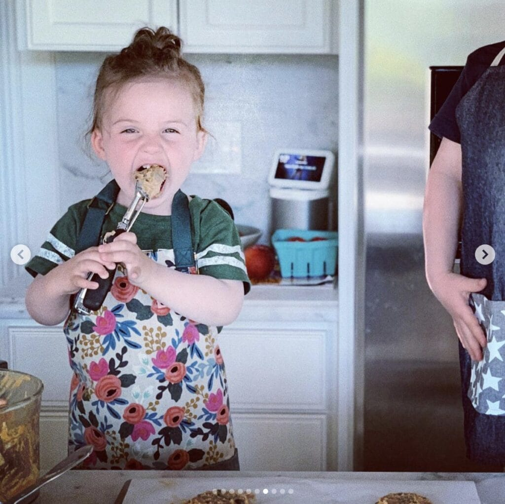 Young girl stands in home kitchen wearing a floral apron and enthusiastically licks batter off a spoon