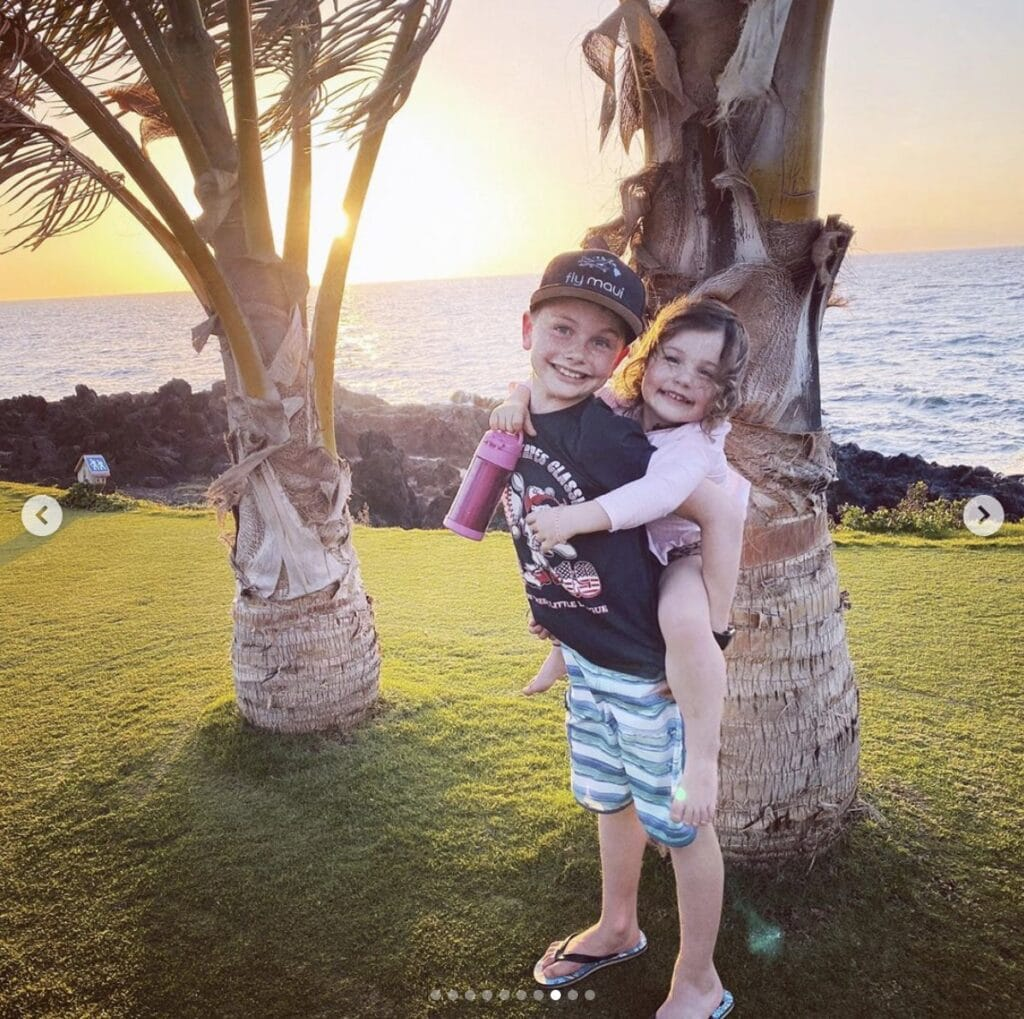 young girl is given a piggyback ride by her older brother. They both smile at the camera while they stand on a lawn that features a sunset over the ocean
