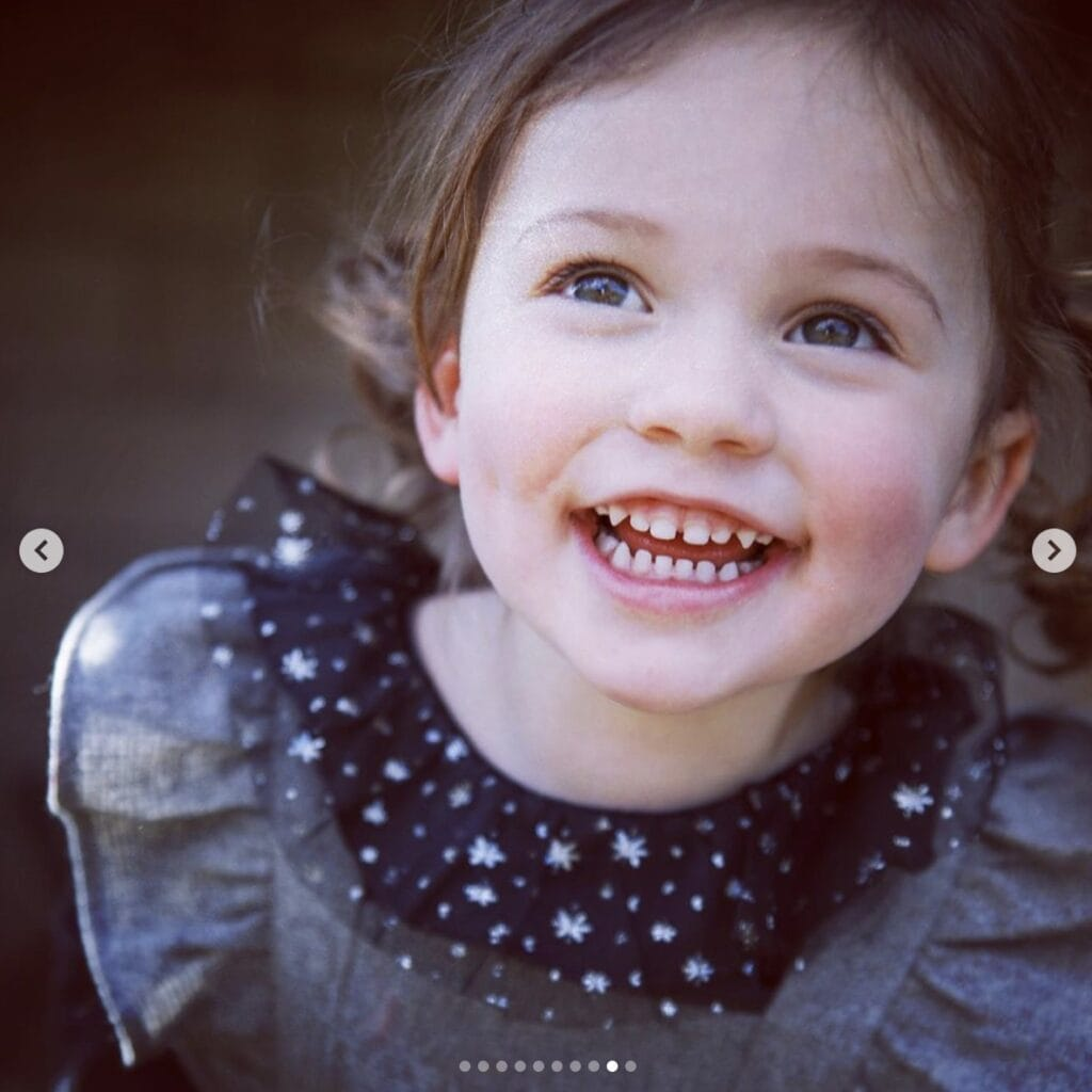 up close picture of young girl smiling gleefully while looking up, looking off camera
