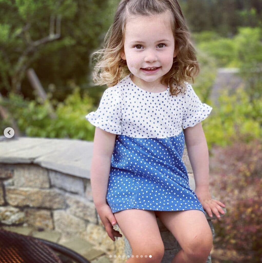 young girl smiles directly at camera wearing a blue and white polka dot dress with ruffled short sleeves