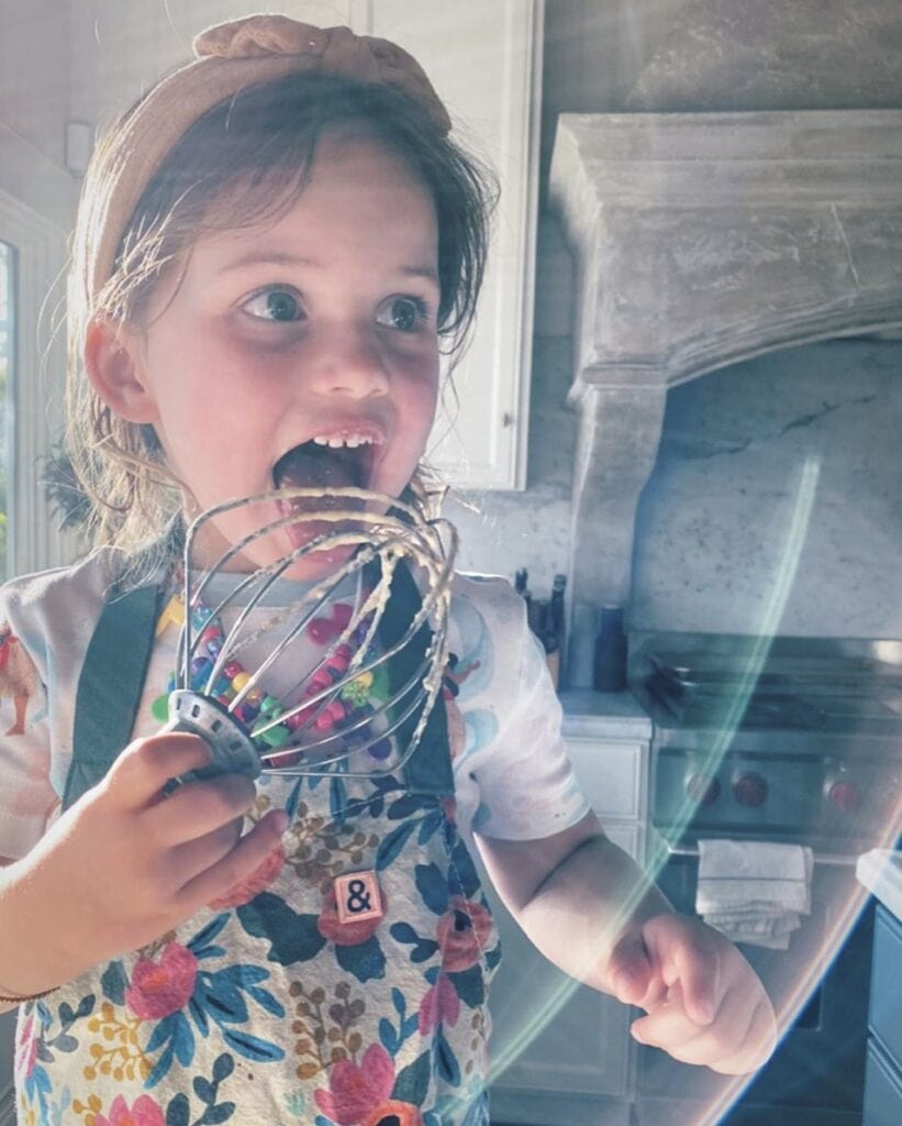 Young girl in home kitchen wears a floral apron and licks batter off a whisk