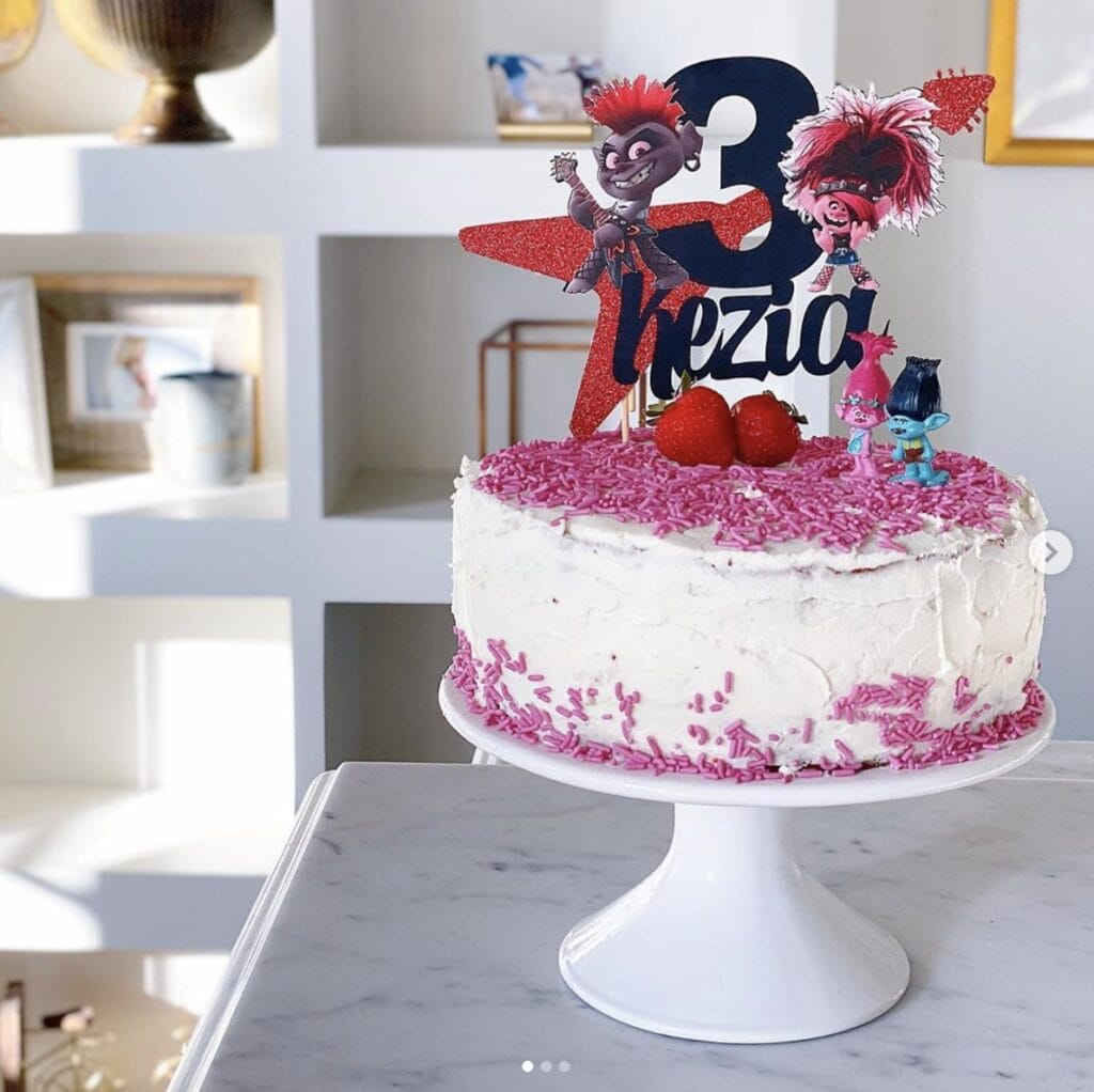 cake with sprinkles and Trolls movie decor with the number three on a white cake stand in home kitchen