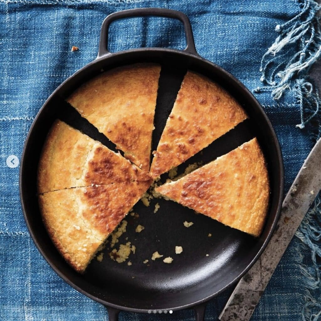 cornbread made in a skillet with several missing slices set on a jean tablecloth