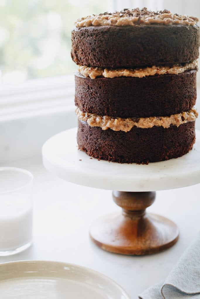 3 layer Gluten Free German Chocolate Cake resting on a cake stand by a window. A glass of milk is next to it.