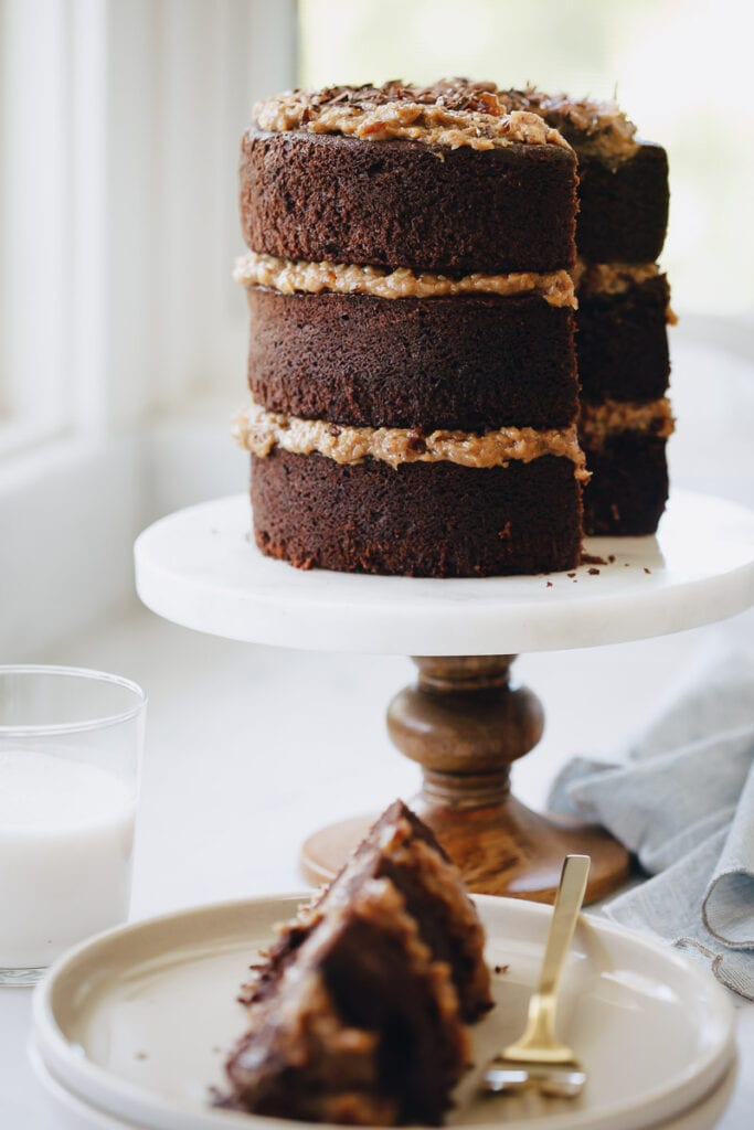 German Chocolate Cake resting on a cake platter and a slice of the cake is on a plate next to it