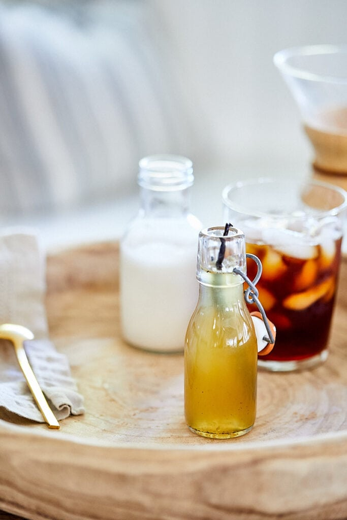 Vanilla Honey Simple Syrup in a glass bottle. Creamer and an iced coffee are in the background.