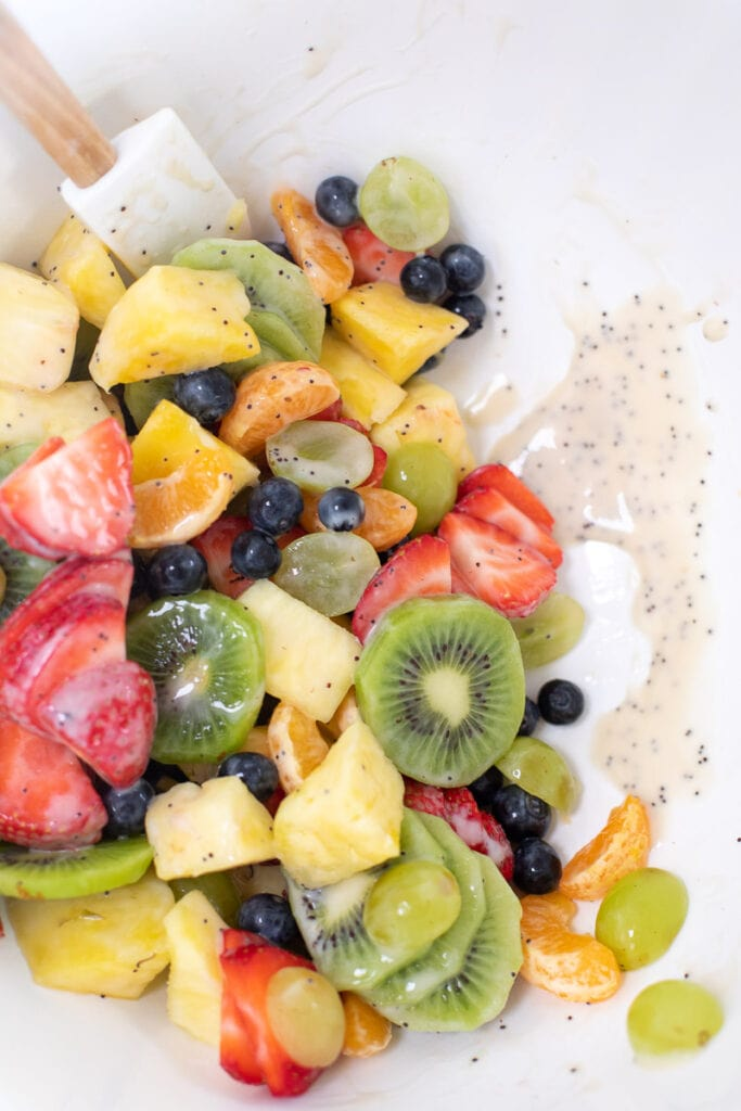 dairy free yogurt in mixing bowl with an assortment of fruit such as kiwi, strawberries, pineapple, blueberries and mandarins