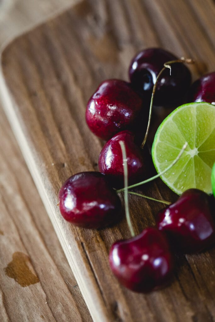 Cherries and lime on a wooden cutting board