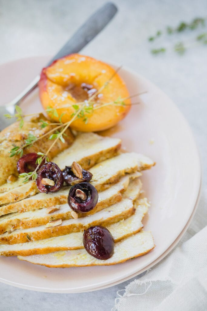 Sliced Spiced Roasted Chicken served on white plate with a peach on the side and cherries as a garnish
