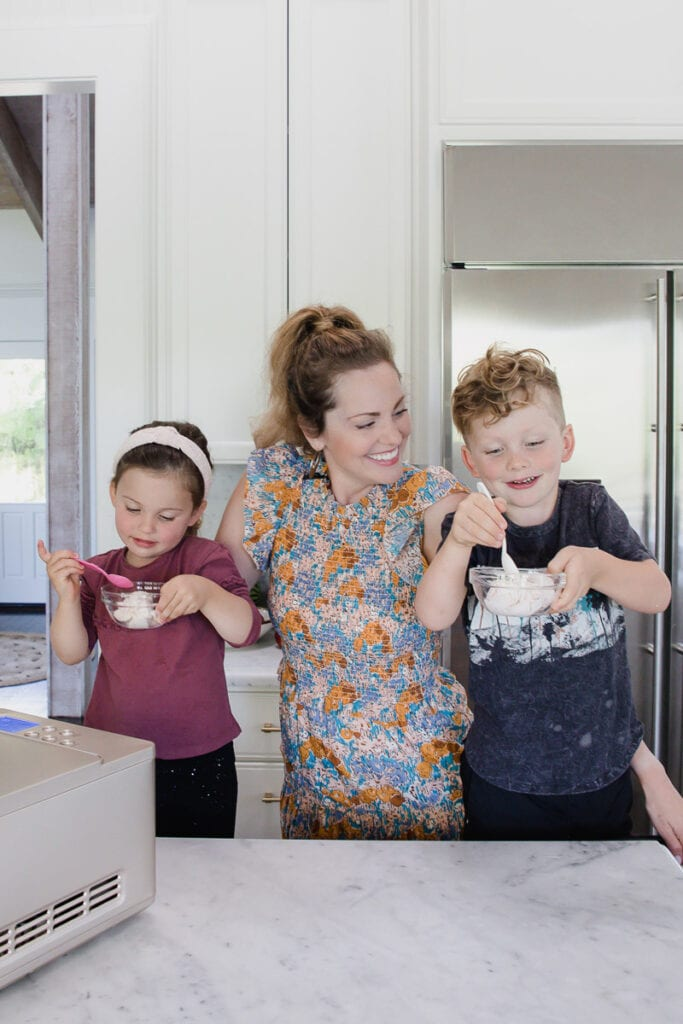 woman stands in kitchen smiling at son & daughter who eagerly dive into their bowls of dairy-free strawberry ice cream