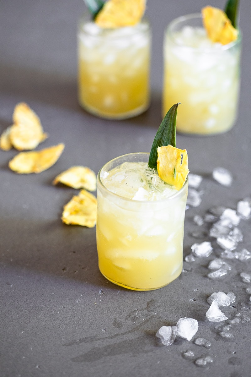 Vanilla Pineapple Margarita in a clear glasses full of ice, garnished with a pineapple slice and leaf