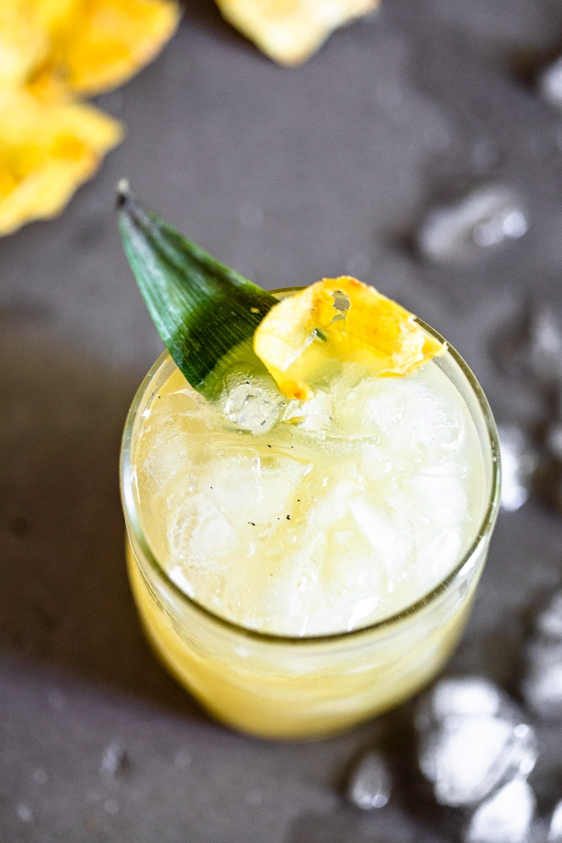 Vanilla Pineapple Margarita in a clear glass full of ice, garnished with a pineapple slice and leaf