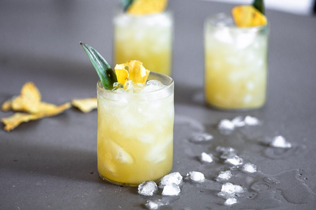 Vanilla Pineapple Margarita in clear glasses full of ice, garnished with a pineapple slice and leaf