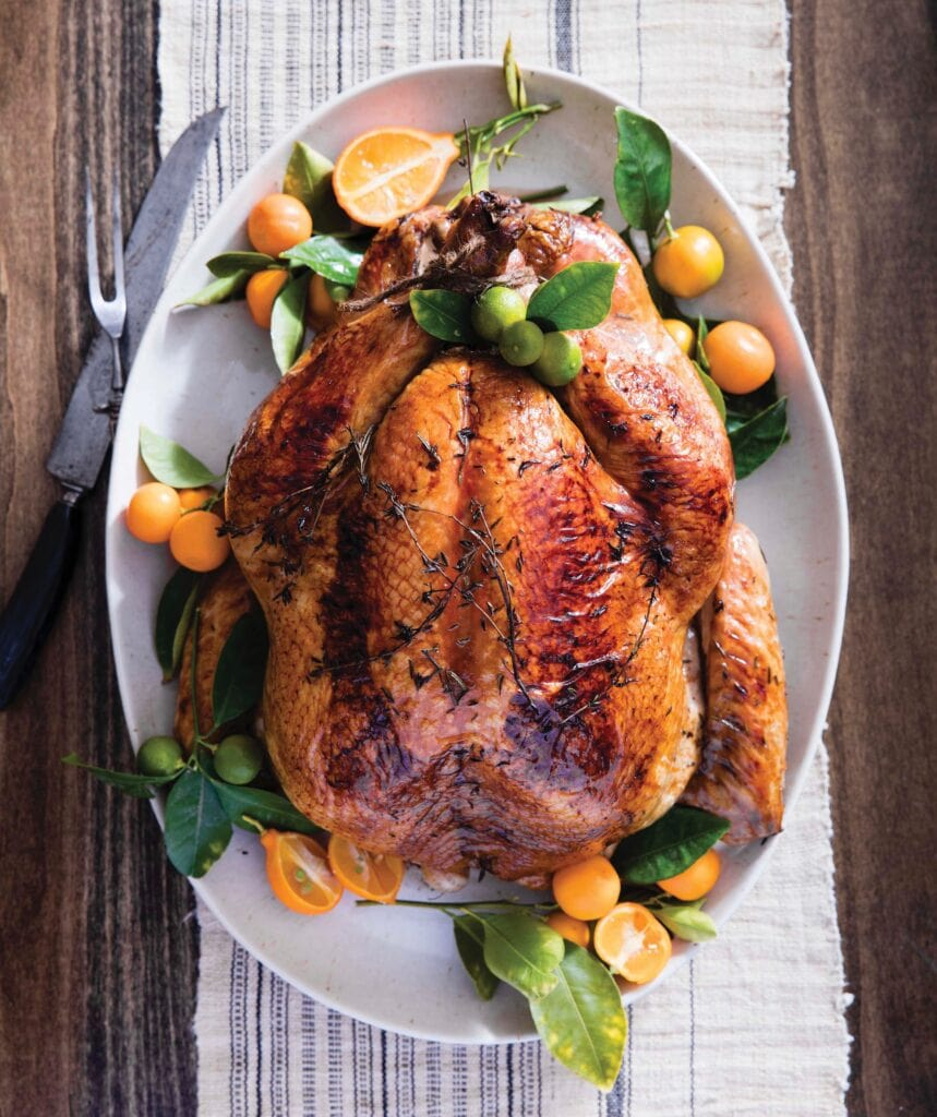 Thanksgiving Turkey fully cooked displayed on a white platter and adorned with small fruit & green leaves